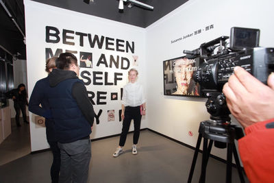 Susanne Junker during an interview in front of her art works